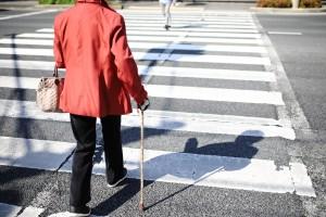 脊柱管狭窄症で杖をつく高齢者